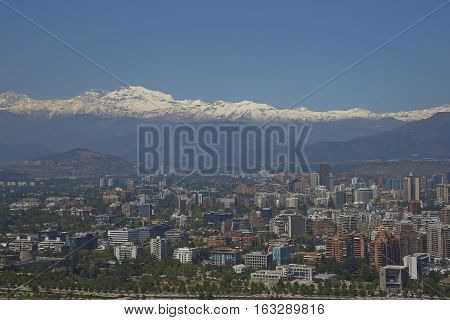 SANTIAGO, CHILE - DECEMBER 27, 2016: View of the Santiago, capital of Chile, from Cerro San Cristobal.  Densely packed modern buildings backed by the snow capped mountains of the Andes.
