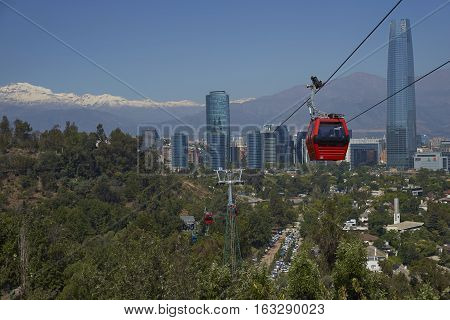 SANTIAGO, CHILE - DECEMBER 27, 2016: Cable car on Cerro San Cristobal in Santiago, Chile.  Beyond, modern skyscrapers of the Las Condes area of the city and snow capped mountains of the Andes.