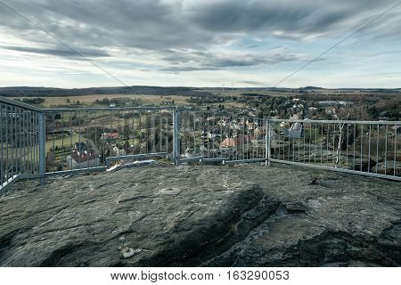 view from rocks with railing to village Tisa in czech Krusne hory mountains in winter without snow