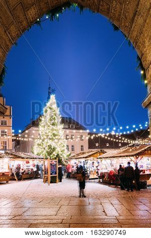 View Of The Town Hall Square - Raekoja Plats Through The Arch Of Town Hall In Tallinn, Estonia. Christmas Tree And Trading Houses With Sale Of Christmas Gifts, Sweets And Mulled Wine. Famous Landmark.