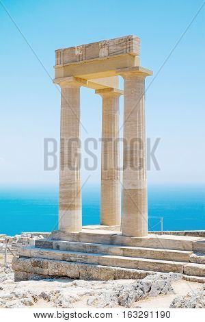 Famous Greek temple pillar against clear blue sky and sea in Lindos Acropolis Rhodes Athena Temple Greece poster