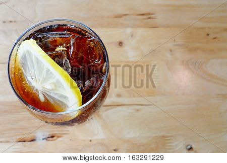 Cola with lemon on wooden background,The cooling drink with ice