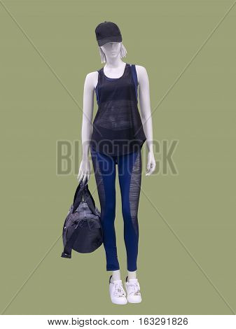 Full-length female mannequin in sportswear over green background. No brand names or copyright objects.