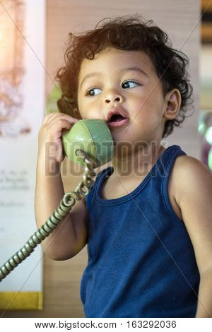 Little Asian Baby Boy Talking On A Retro Telephone.