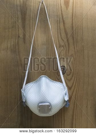 Industrial respirator with valve hanging on a wooden board.