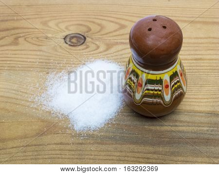Ceramics saltcellar with salt on wooden background