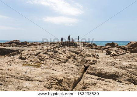 Four People Fishing On Rocks On Early Morning Beach