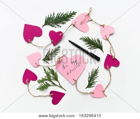 Bright pink paper hearts connected with a rope. Cards for Valentine's day decorated with thuja branches Be My Valentine handwritten text. Flat lay on white background top view