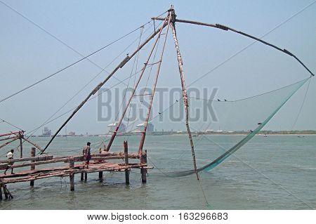 People Are Walking Near Chinese Fishing Nets In Kochi