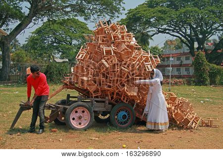 Man And Woman Are Unloading A Cart With Cargo Of Stools
