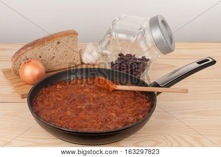 Chili Con Carne in pan on wooden table on background onion, garlic, bread and beans
