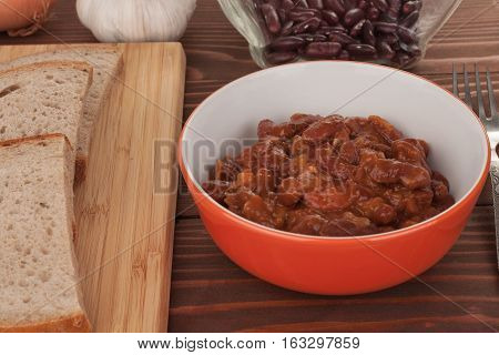 Chili Con Carne in bowl on wooden table, around onion, garlic bread, and beans