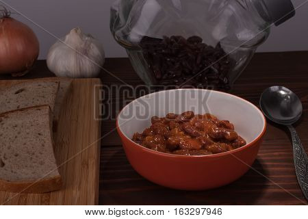 Chili Con Carne in pan on wooden table on background, onion, garlic, bread, and beans