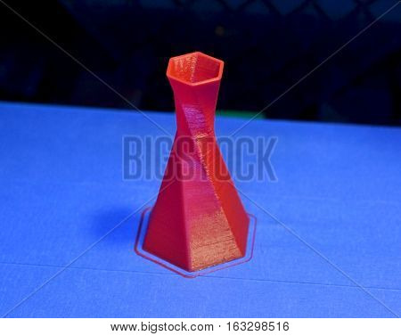 Model is printed on the 3D printer close. 3D printer printing object red color on the basis of blue and black background close-up. Modern 3d printing technology