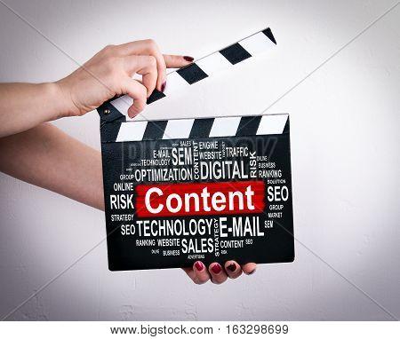 Content concept. Female hands holding movie clapper.