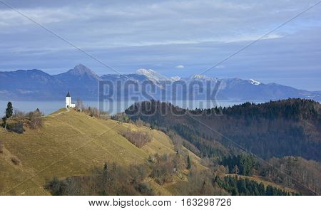 The Church of Saints Primus and Felician near Jamnik in north west Slovenia with the Julian Alps in the background.