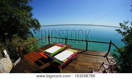 Relaxing, quiet and peaceful life at multi-colored lagoon Bacalar, Quintana Roo, Mexico. Deck chair and pier.