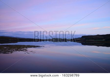 Pastel skies and a calm Loch Dunvegan in Scotland.