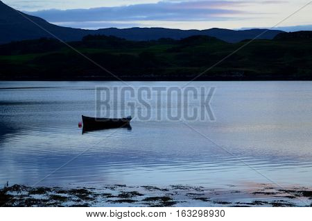 Silhouetted boat on Loch Dunvegan on the Isle of Skye.