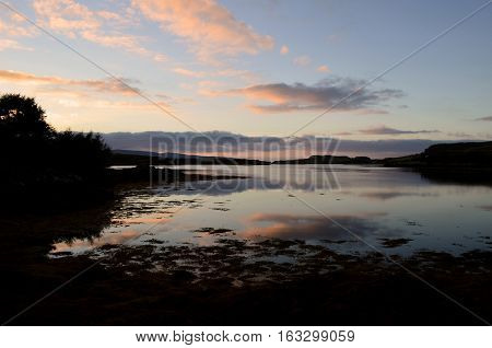 Pastel clouds reflecting in Loch Dunvegan at dawn.