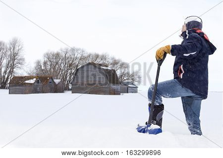 horizontal image of a man trudging through deep snow with his shovel with a barn and shed in the background on a cold winter day.
