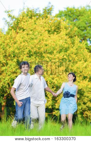 Family Values Concepts and Ideas. Caucasian Family of Three Having Fun Together and Running in Summer Forest With Joined Hands. Vertical Image Orientation