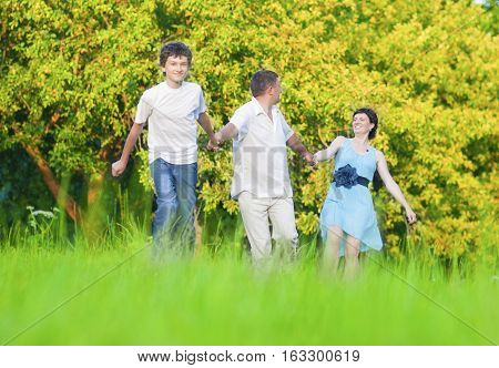 Family Values Concepts and Ideas. Caucasian Family of Three Having Fun Together and Running in Summer Forest With Joined Hands. Horizontal Image Orientation