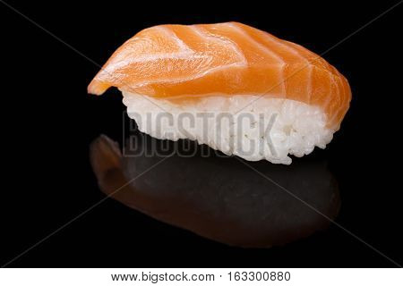 Close-up of Sake sushi with salmon on a black background with reflection. Japanese cuisine