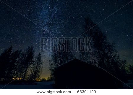Old barn and trees in starry night landscape