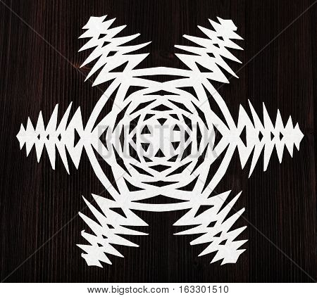 Snowflake Carved From Paper On Dark Brown Board