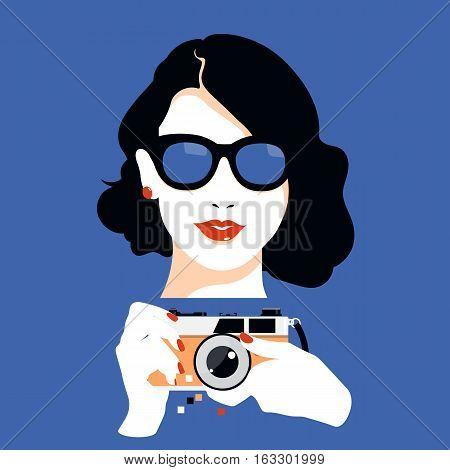 Pretty girl in big glasses holding vintage camera
