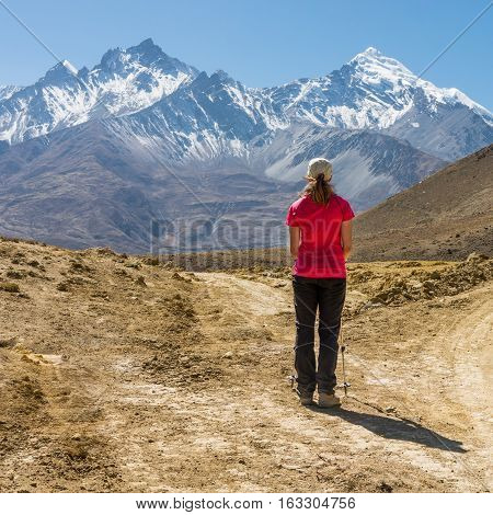 Lonely trekker on a crossroad of two roads towards mountains. Annapurna circuit trek in Nepal.