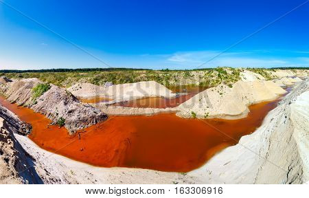 multi bucket excavator, giant stacker, sand quarry filled with water saturated with red color minerals