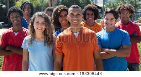 Large group of standing young man and woman outdoor in the summer in the city