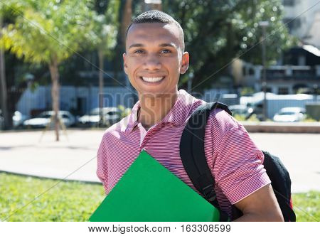 Laughing mexican male student in the city in the summer