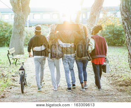 Group of friends walking in city park with train and sun light in background - Young people having fun in university break - Leisure after school concept - Focus on center heads - Warm filter