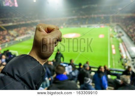Soccer fan celebrate their team in football italian stadium - Hooligans people watching sport match - Love for sport concept - Focus on man close hand - Warm filter with original stadium lights