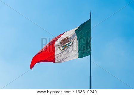 Flag of Mexico in the wind on a sunny day against the blue sky.