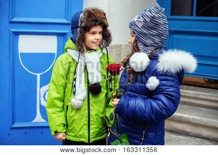 The little boy gave the girl rose. The concept of love and Valentine's Day.
