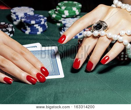 hands of young caucasian woman with red manicure at casino green table close up, off-line concept