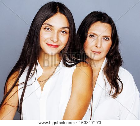 cute pretty teen daughter with mature mother hugging, fashion style brunette makeup close up tann mulattos, lifestyle people concept close up