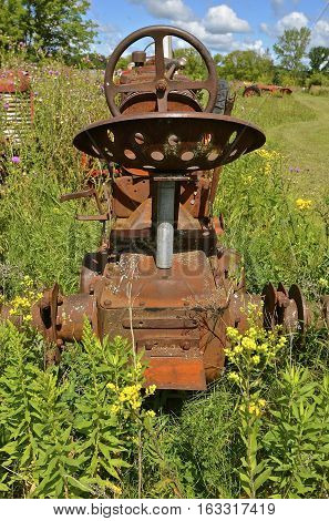 The reinforced seating apparatus and steering wheel of a old tractor is found in the weeds and long grass