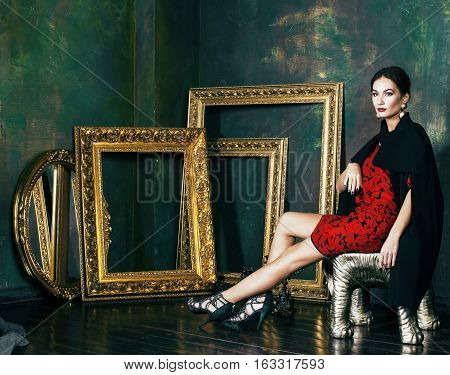 beauty rich brunette woman in luxury interior near empty frames, vintage elegance brunette close up