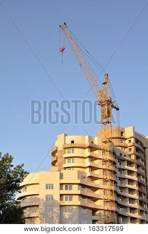 Boom mobile crane yellow. Green trees. New development.