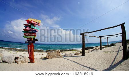 Colorful direction indicator signs to other country at the Caribbean beach in Punta Sur Park, Quintana Roo, Cozumel island, Mexico.
