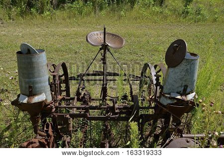An old rusty corn planter with double seed canisters to hold the seed
