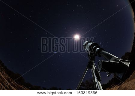 Telescope standing in the desert high mountains in the night pointing to the clear sky with stars and moon