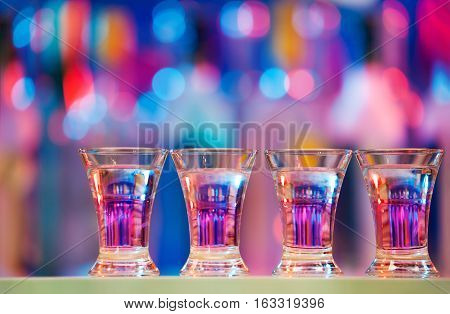 Picture of four burning drinks in shot glasses standing in a row on a bar counter with copy-space