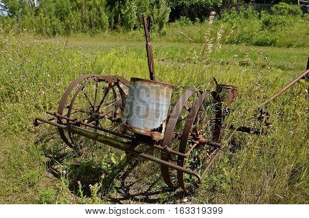 An old rusty corn planter with a single canister for holding the seeds.