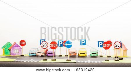 Picture of playing set of road signs and paper cars in a parking maquette with copy-space